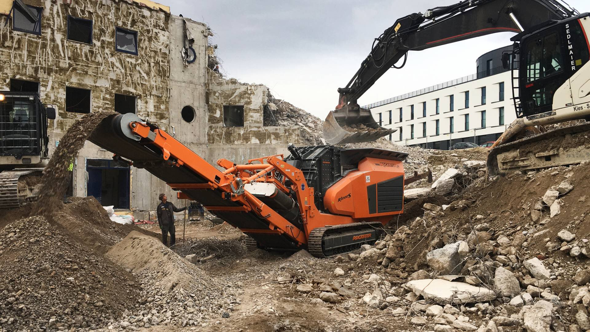Gallery image 1 - CONSTRUCTION WASTE - Rockster R1000S track-mounted impactor crushes 180-200t/h heavily reinforced demolition debris to 0-50mm.